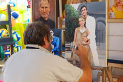 Street painter makes a copy from photo of young couple on canvas Royalty Free Stock Photo