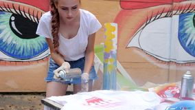 Street painting, girl with spray paint in hand, adolescent with aerosol paint at background of graffiti in slow motion