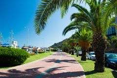 A street with palm trees near the port of Alanya. Port of Alanya. Alanya is a beach resort city and a component district of Antalya Province on the southern royalty free stock images