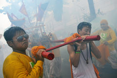 Street Parade of the Nine Emperor Gods Festival. Devotees of a Chinese Taoist shrine carry a palanquin housing a Chinese God idol while firecrackers explode Royalty Free Stock Photography