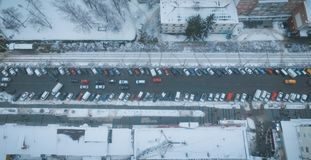 Street parking with snow covered cars during frosty winter sunrise. View from above stock photography