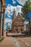 Street with people, brick buildings, steeple with golden clock and sunny blue sky in Amsterdam. Royalty Free Stock Photography