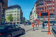 Street with people and cars near metro station Rathausmarkt and town hall Rathauson the market square, near lake Alster royalty free stock photo