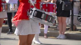 Street performance of festive march of drummers girls in red costumes on city street. Close-up of female hands drummers. Young girls drummer in red at the parade stock video