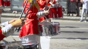 Street performance of festive march of drummers girls in red costumes on city street. Young girls drummer in red at the parade. Street performance on the stock footage