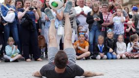 Street performance, young man with ball doing trick into front of viewers at city area in slow motion. Wroclaw, Poland 12 May 2018: street performance, young man stock footage