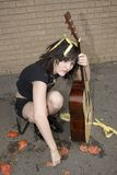Street Performer. Young street performer pelted with tomatos and bananas sits broken hearted with her guitar Royalty Free Stock Photos