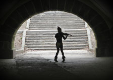 Street performer. A silhouette of a street performer dancing and playing violin in a tunnel Royalty Free Stock Images