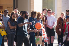 Street performer with basketball in front of crowd. Adelaide, Australia - February 20, 2017: A street performer entertains a crowd in Rundle Mall with a series Stock Photos