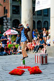 Street performer balances on top of a wine bottle. Royalty Free Stock Images