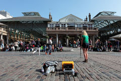 Street Performer in Covent Garden in London. Entertainer performs with two female tourists in Londons Covent Garden Square Stock Photo