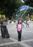Street performer creating oversize bubbles for kids at Central Park in New York Royalty Free Stock Photography