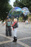 Street performer creating oversize bubbles for kids at Central Park in New York Royalty Free Stock Image