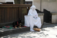 Street Performer and Dog Resting. A living-statue street performer resting between acts Royalty Free Stock Photos