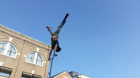 Street performer doing hand stand. Street performer at a festival in the city does an aerial handstand with split legs Stock Photos