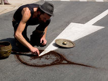 Street performer draw a symbol on the asphalt. Royalty Free Stock Photos