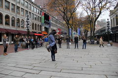 Street performer drawing a crowd that watches him leap over a tourist from the crowd,Faneuil Hall,Boston,Mass,2014 Royalty Free Stock Images
