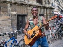 Street performer with guitar poses outside Eglise Saint Eustache Royalty Free Stock Photos
