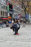 Street performer leaping over row of tourists,Faneuil Hall,Boston,Mass,2014 Stock Image