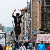 Street performer on the rope. Edinburgh, Scotland - September 14, 2014: street performer walking on a rope while holding a violin in his hand. The High Street Royalty Free Stock Photos
