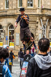 Street performer on the rope while playing the violin. Edinburgh, Scotland - September 14, 2014: street performer balancing on a rope while playing a violin. The Stock Photography