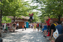 Street performer springs up and flips for the crowd. Stock Image