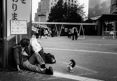 Street performer in Tokyo. Tokyo, Japan - April 26, 2015: A street artist in Tokyo poses lifelessly with a cute toy.  The sign reads 'Don't worry. I'll catch up Stock Photo