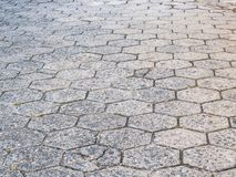 Street of hexagonal concrete blocks, badly preserved. Street perspective texture of hexagonal concrete blocks, poorly maintained and deteriorated Stock Photo