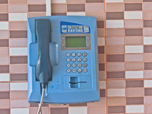 Street phone. Turquoise hanging on the wall, lined with tiles of different colors Stock Photo