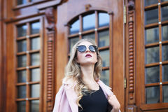 Street photo of beautiful young fashionable woman with sunglasses looking up. Female fashion. Closeup portrait Royalty Free Stock Photos