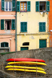 Street photo of house and colorful boats on wall. Manarola. Ligu Stock Images