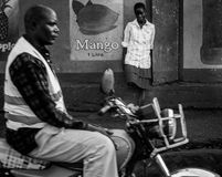Street photo. Jinja, Uganda -September 2015 - A boda boda cyclist, the foreground, and a random young lady on the streets of Jinja Royalty Free Stock Photos