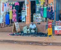 Street photo. Jinja, Uganda -September 2015 - A street vendor waits for customers at his stock Royalty Free Stock Photography