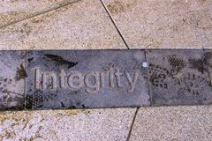 Street photo of word Integrity carved into pavement royalty free stock images