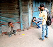 Street photographers taking photo of a beggar Royalty Free Stock Image