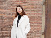Street photography of a beautiful Chinese woman in white coat with red brick wall background, looking at you with two hands in her royalty free stock photo