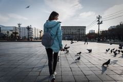 Street Photography: A girl tourist walks around the town square among pigeons. A backpack at the back. royalty free stock photo