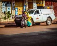 Street photography. Jinja, Uganda -September 2015 - An old woman walks passed a parked car in Jinja town Royalty Free Stock Photos