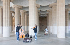 Street players and a girl a park guell. Two players of violin and bass at park guell, with girl going in her skateboard Stock Photography