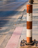 Street pole. Industrial metal street pole in red and white color jointed on concrete footpath serves to divide the space between road and walkway stock photography