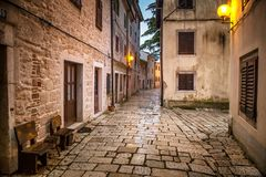 Street in Porec town illuminated by lamps at the evening. Royalty Free Stock Image