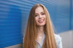 Emotional close up portrait of a adult pretty blonde woman with gorgeous extra long hair posing outdoors against blue grey striped Royalty Free Stock Photography