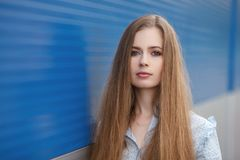 Emotional close up portrait of a adult pretty blonde woman with gorgeous extra long hair posing outdoors against blue grey striped Stock Photos