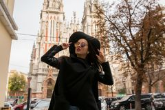 Street portrait of attractive model in trendy black coat and sty. Street portrait of attractive woman in trendy black coat and stylish hat. Female fashion Stock Image
