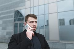 Street portrait of a beautiful man with a beard communicating on the phone against the backdrop of a modern building. Business portrait Royalty Free Stock Photography