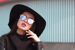 Street portrait of beautiful woman in trendy black coat and styl. Ish hat.Female fashion concept Stock Photo