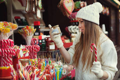 Street portrait of beautiful young woman choosing some sweets on the festive Christmas fair. Lady wearing classic Stock Photos