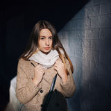 Street portrait of a cute young brunette girl in coat and scarf Royalty Free Stock Photo
