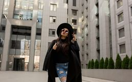 Street portrait of fashionable model in trendy black coat and st. Street portrait of fashionable woman in trendy black coat and stylish hat posing near mall Royalty Free Stock Image