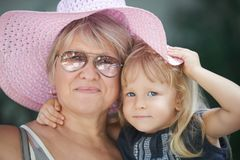Street portrait of the grandmother with the granddaughter in a pink summer hat.  stock images